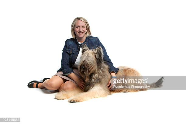 Dog trainer with Briard dog on white backdrop