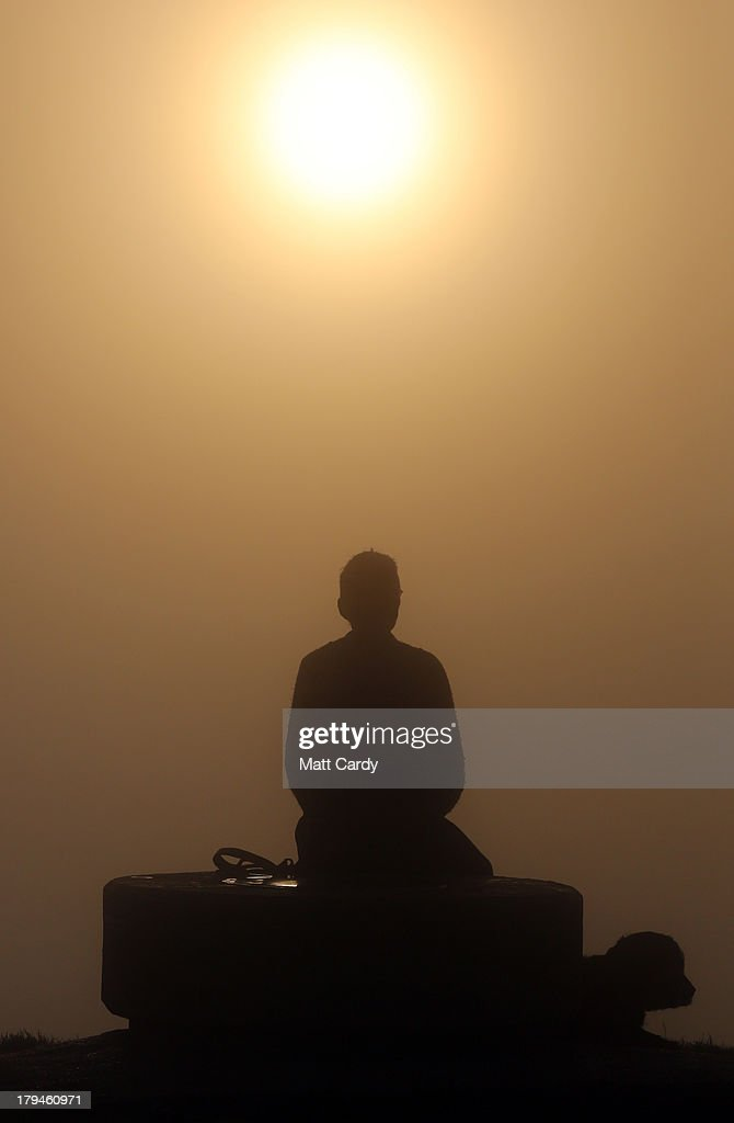 A dog walker takes in the view at the top of Glastonbury Tor as the rising sun begins to clear the early morning mist and fog near the town of Glastonbury on September 4, 2013 in Somerset, England. Parts of the UK are set to enjoy a late summer heatwave today, with temperatures possibly reaching 28C in central, eastern and southern England, with temperatures predicted to climb even higher tomorrow.