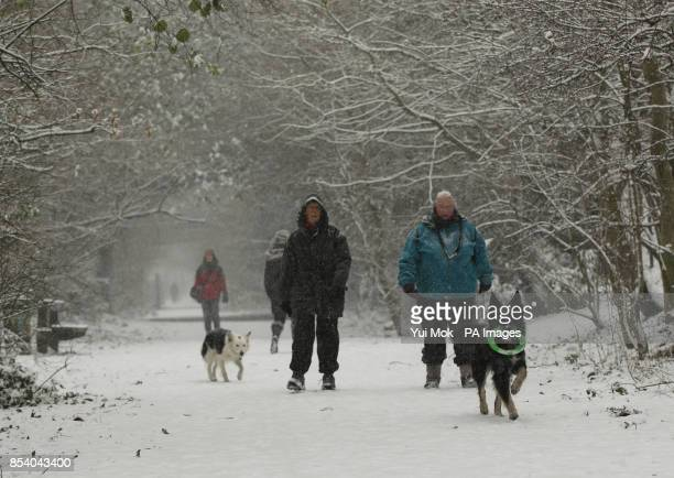 Dog walkers in the snow along the Parkland Walk nature reserve trail in north London