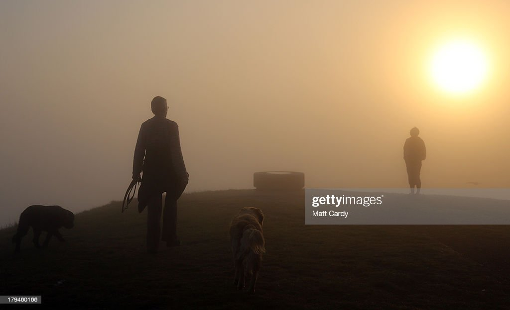 Dog walkers walk to the top of Glastonbury Tor as the rising sun begins to clear the early morning mist and fog near the town of Glastonbury on...