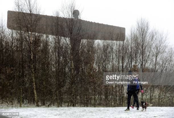 Dog walkers walking in the snow by the Angel of the North