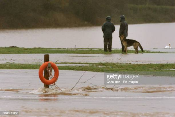 Dog walkers wander through fields beside the River Usk which burst its banks in Abergavenny Wales The Environment Agency Wales confirmed three severe...