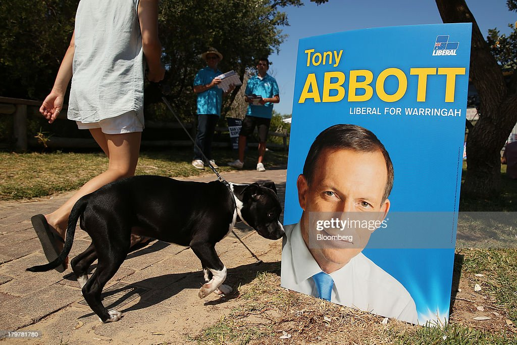A dog walks past a poster for Australia's Opposition Leader Tony Abbott displayed outside the polling station at the Freshwater Surf Life Saving Club in Sydney, Australia, on Saturday, Sept. 7, 2013. Australian voters are heading to eject the Labor party after six years in power, with opinion polls showing they will put Abbott's Liberal-National coalition in charge of the $1.5 trillion economy. Photographer: Brendon Thorne/Bloomberg via Getty Images