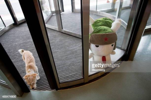 A dog walks through a revolving door as a plush toy of Mitu rabbit the Xiaomi Corp mascot stands on display at a Xiaomi Corp office in Beijing China...