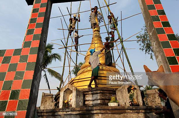 A dog watches as Burmese villagers help repair the top of a pagoda damaged during cyclone Nargis at the Dha Ma Thukha monastery April 26 2009 in the...