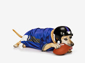 Dog wearing football helmet and jersey chewing on football