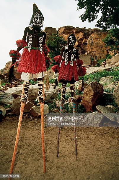 Dogon dancers performing the Dama ritual dance on stilts and wearing Kanaga masks Mali