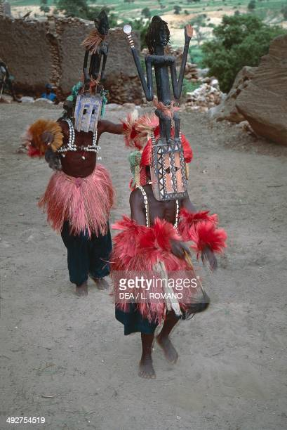 Dogon dancers performing the Dama ritual dance wearing Kanaga masks Mali