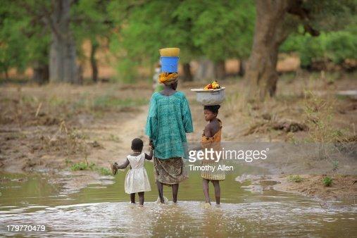 Dogon family walk through flood water, Mali