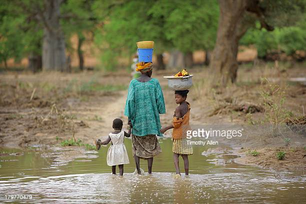 Dogon family walk through flood water, Mali