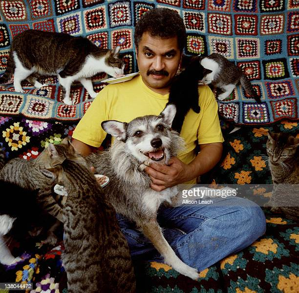 Dogowner Philip Gonzalez is photographed holding his dog Ginny who was named 'Cat of the Year' in 1998 eulogized for his uncanny skill and bravery in...