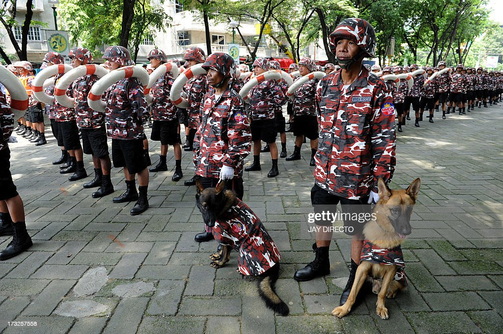 K-9 dogs join Metropolitan Manila Development Authority(MMDA) rescue personnel as they parade in an earthquake and rescue drill at a government school in Manila on July 11, 2013. The event is part of the 11th Asian Crisis Management Conference as civil defence officials of seven countries along with international aid groups met in the Philippine capital for a two-day conference on disaster management looking at how Asian cities can recover from devastating disasters. AFP PHOTO / Jay DIRECTO