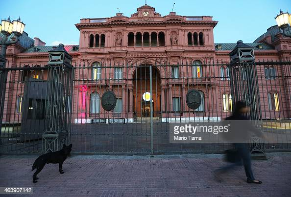 A dogs stands as a woman walks past the front of the Casa Rosada presidential palace on February 19 2015 in Buenos Aires Argentina A large 'Silent...