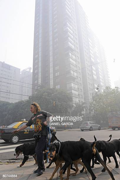 A dogwalker crosses a street as a haze of smoke engulfs Buenos Aires in the morning of April 18 2008 Massive brush fires set by cattle ranchers and...