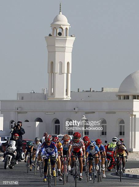 A peloton of cyclists pass a mosque on the road to alKhor during the women's road race during the 15th Asian Games in Doha 04 December 2006...