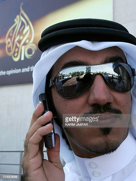 A Qatari man talks on his mobile phone as the logo of the Qatarbased AlJazeera satellite channel appears in the background in Doha 01 November 2006...