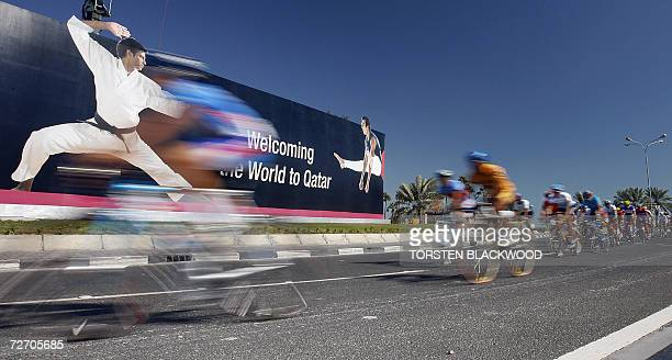 Cyclists streak down the Corniche boulevard at the start of the men's road race during the 15th Asian Games in Doha 03 December 2006 Fortysix riders...