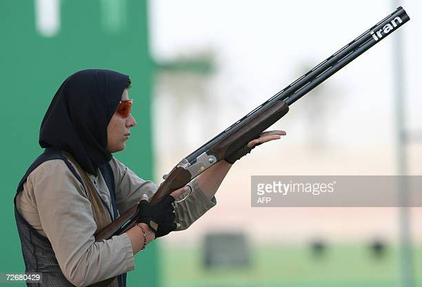 Iran's Masomeh Ameri aims during a trap shooting training session 30 November 2006 one day before the 15th Asian Games officially open More than...