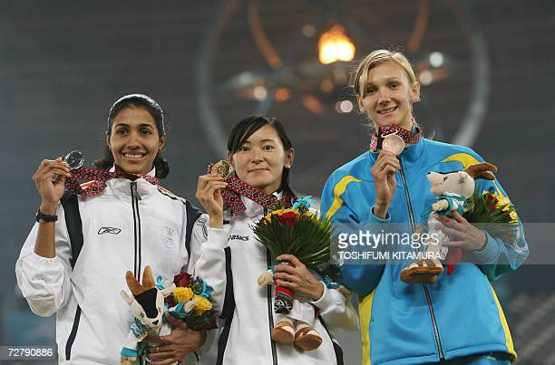 Japan's Kumiko Ikeda poses with India's Anju Bobby George and Kazakhstan's Olga Rypakova at the awards ceremony for the women's long jump final on...