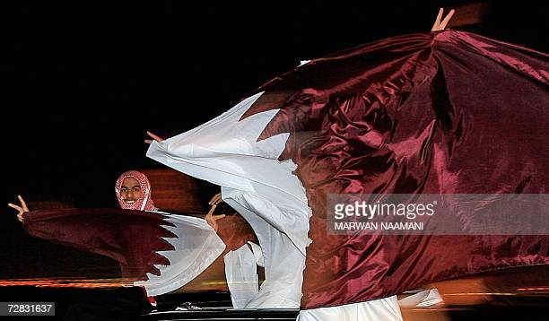 Qatari youths celebrate with national flags in the streets of Doha after Qatar's football team won the gold medal match between Qatar and Iraq at the...