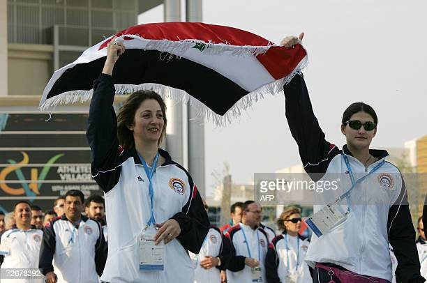 Syrian athletes hold up their flag as they arrive to attend their welcoming ceremony in the athletes village at the 15th Asian Games in Doha 30...