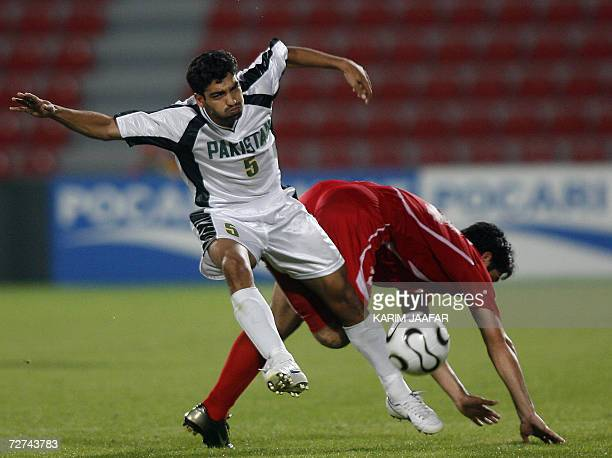 Syrian national team football player Rafe Raja vies with Samar Ishaq of Pakistan during their Men's Round 2 Group F Match at the 15th Asian Games at...