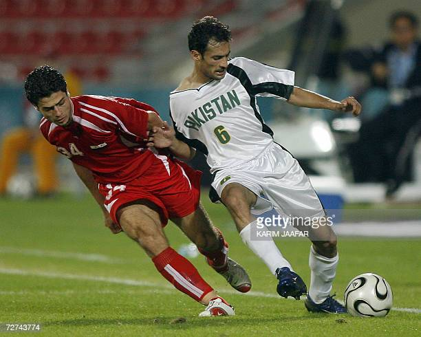 Syrian national team football player Wael Ayan vies with Adel Ahmed of Pakistan during their Men's Round 2 Group F Match at the 15th Asian Games at...