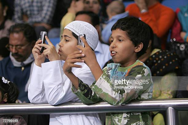 Young Qatari fans take pictures with their mobile phones at the Women's Freestyle Wrestling competition between Japan and South Korea during the 15th...