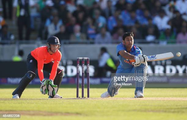 Dohni of India hits out as Jos Buttler of England looks on during the NatWest International T20 2014 match between England and India at Edgbaston on...