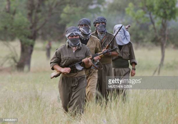 Kurdistan PKK fighters jog with their rifle during a training session early in the morning 20 June 2007 at Amedia area in Northern Iraq 10 km near...