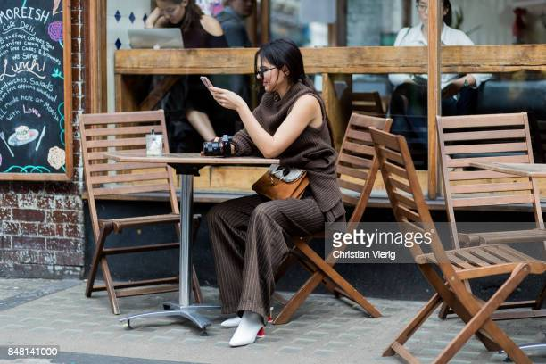 Doina Ciobanu sitting in a cafe outside JW Anderson during London Fashion Week September 2017 on September 16 2017 in London England