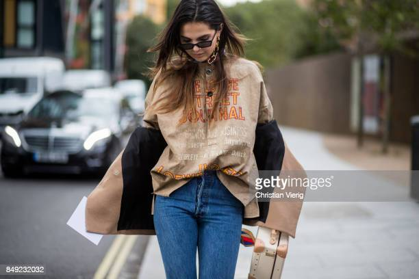 Doina Ciobanu wearing brown top denim jeans ankle boots outside Christopher Kane during London Fashion Week September 2017 on September 18 2017 in...