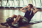 Handsome sporty young man doing sit-up on floor in gym