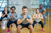 A group of adults are taking a fitness class together. They are arranged in rows and are smiling at the camera while doing squats.