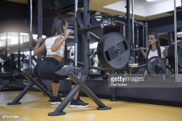 Kniebeugen mit Langhantel in einem Fitnessstudio zu tun