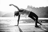 Young woman doing yoga by the lake. Black and white image