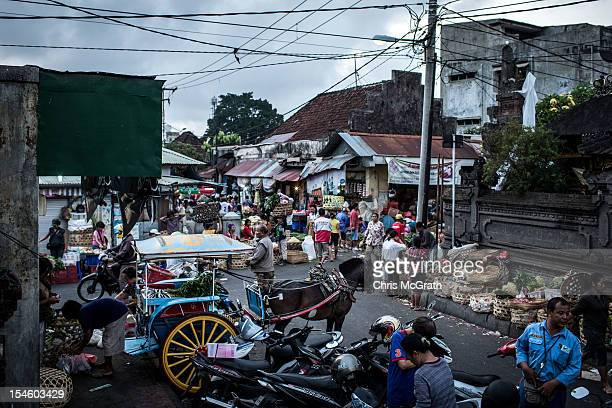 Dokar driver Nyoman Yasa 35 loads produce into his dokar at the Badung market on October 15 2012 in Denpasar Bali Indonesia The Dokar is traditional...