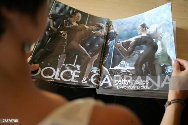 STORY 'Dolce Gabbana veut dsamorcer la polmique sur sa nouvelle campagne de pub'=== A woman looks at a magazine showing the latest Italian couture...