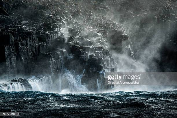 Dolerite cliff with waves under ray of light