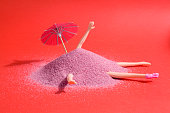 Arm and leg's doll emerging from a pile of pink sand as if it were hiding. Minimal funny and quirky design still life photography