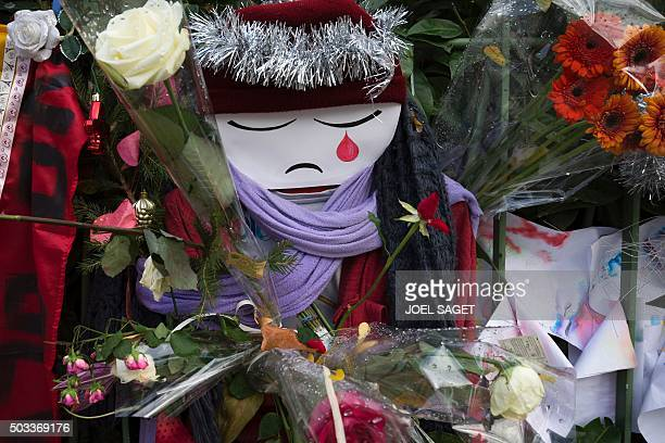 TOPSHOT A doll crying is seen among flowers at a makeshift memorial in tribute to the victims of the Paris terror attacks on January 4 outside the...