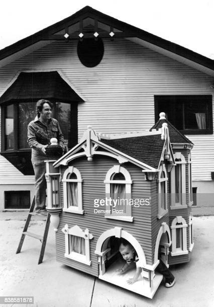 Doll Houses Tiny Town homebuilder David M Gerace looks over as his grandson 18monthold Alexander looks under the poarch of the newest addition to the...