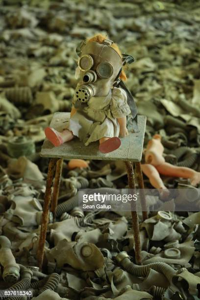 A doll likely arranged by a tourist dressed with a gas mask sits on a chair among hundreds of gas masks lying on the floor of abandoned School Number...
