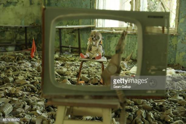 A doll likely arranged by a tourist dressed with a gas mask sits on a chair among and old television and hundreds of gas masks lying on the floor of...