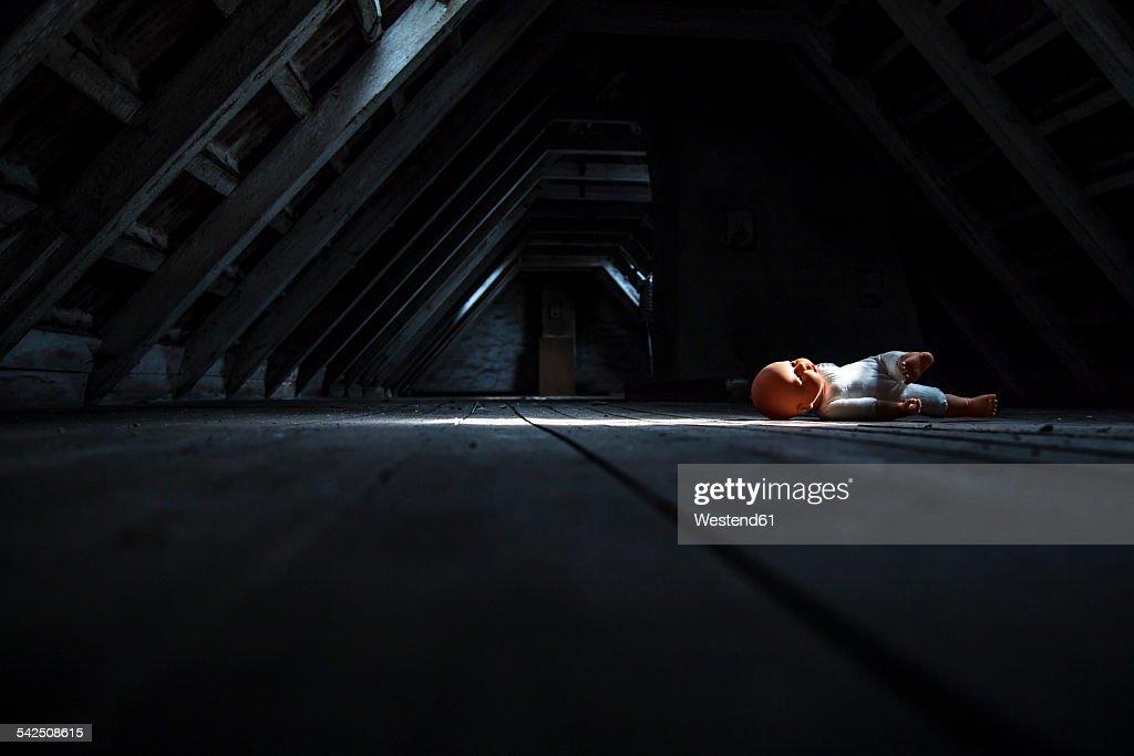 Doll lying at empty dark attic