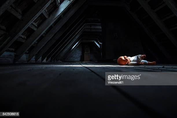 Doll lying at empty dark attic