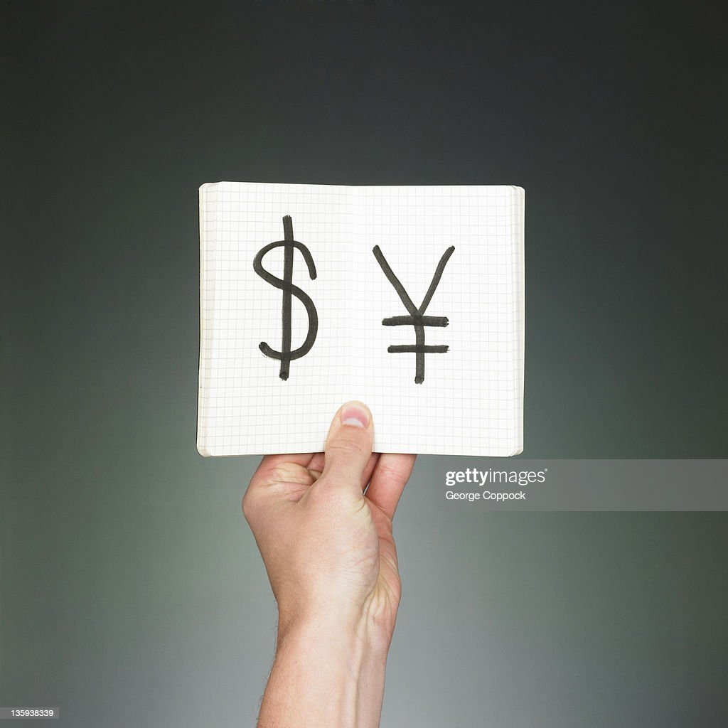 US Dollar and Chinese Yen symbol in notebook : Stock Photo
