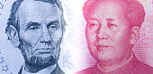 US dollar bill and China yuan banknote portraits with copy space