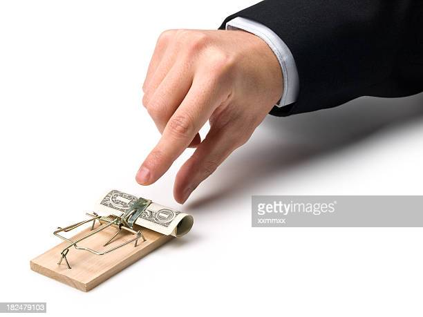 Dollar bill in a mouse trap lures in business man