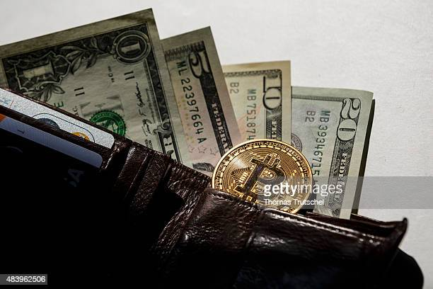 Dollar bills and a Bitcoin put in a wallet on August 14 in Berlin Germany